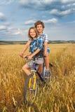 Retrato de un adolescente en una bicicleta que viaja en campo del centeno Fotos de archivo