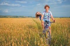 Retrato de un adolescente en una bicicleta que viaja en campo del centeno Foto de archivo libre de regalías