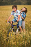 Retrato de un adolescente en una bicicleta que viaja en campo del centeno Imágenes de archivo libres de regalías