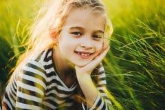 Retrato de un adolescente en una camiseta rayada entre la alta hierba verde Imagen de archivo libre de regalías