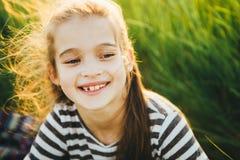 Retrato de un adolescente en una camiseta rayada entre la alta hierba verde Foto de archivo libre de regalías