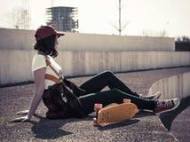 Retrato de un adolescente en una gorra de béisbol y un monopatín Fotografía de archivo libre de regalías