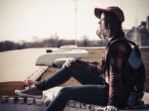 Retrato de un adolescente en una gorra de béisbol y un monopatín Fotografía de archivo