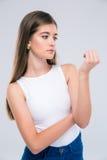 Retrato de un adolescente femenino que mira sus clavos Foto de archivo libre de regalías