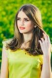 Retrato de un adolescente hermoso en un vestido amarillo contra un fondo del verdor Imagen de archivo libre de regalías