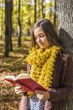 Retrato de un adolescente hermoso que lee un libro en la delantera Imagenes de archivo
