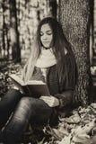 Retrato de un adolescente hermoso que lee un libro en las delanteras Fotografía de archivo libre de regalías