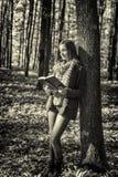 Retrato de un adolescente hermoso que lee un libro en las delanteras Imagen de archivo libre de regalías