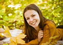 Retrato de un adolescente hermoso que se divierte en parque del otoño Imagen de archivo libre de regalías