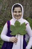 Retrato de un adolescente hermoso que sostiene una sola hoja Fotos de archivo libres de regalías