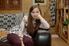 Retrato de un adolescente joven que se sienta en el sofá Foto de archivo libre de regalías
