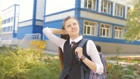 Retrato de un adolescente de la colegiala con una mochila cerca de la escuela El adolescente de la muchacha endereza la situación almacen de metraje de vídeo