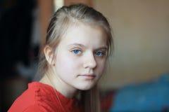 Retrato de un adolescente de la muchacha de los ojos azules del pelo rubio en casa Fotos de archivo libres de regalías
