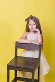 Retrato de un adolescente lindo en un fondo amarillo en la silla Fotos de archivo