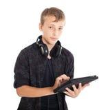 Retrato de un adolescente lindo con los auriculares y el ordenador de la tableta. Imagenes de archivo