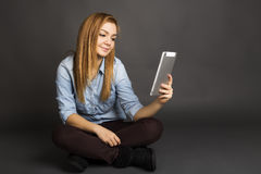 Retrato de un adolescente lindo usando una tableta digital mientras que se sienta Fotos de archivo