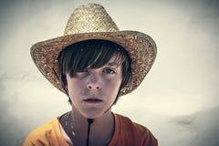 Retrato de un adolescente masculino con el sombrero de paja Imagen de archivo libre de regalías
