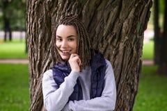 Retrato de un adolescente positivo con las trenzas trenzadas Ella sonríe ampliamente y mira con confianza Fotografía de archivo libre de regalías