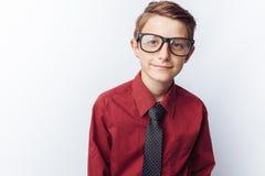 Retrato de un adolescente positivo en un fondo blanco, vidrios, camisa roja, publicidad, parte movible del texto Fotos de archivo