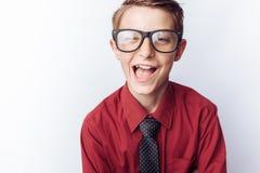 Retrato de un adolescente positivo en un fondo blanco, vidrios, camisa roja, publicidad, parte movible del texto Imágenes de archivo libres de regalías