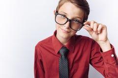 Retrato de un adolescente positivo en un fondo blanco, vidrios, camisa roja, publicidad, parte movible del texto Imagen de archivo