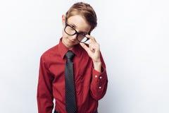 Retrato de un adolescente positivo y coqueto, en un fondo blanco, vidrios, camisa roja, tema del negocio, publicidad, Imágenes de archivo libres de regalías