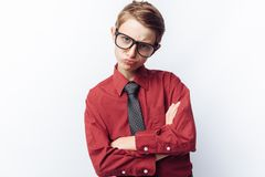 Retrato de un adolescente positivo y emocional, fondo blanco, vidrios, camisa roja, tema del negocio, publicidad, Imagen de archivo libre de regalías
