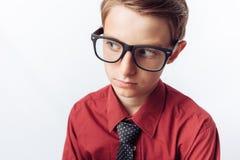Retrato de un adolescente positivo y pensativo, fondo blanco, vidrios, camisa roja, tema del negocio, publicidad, Fotografía de archivo libre de regalías