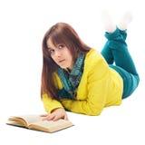 Retrato de un adolescente que miente en el libro de lectura del suelo Imagen de archivo