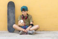 Retrato de un adolescente que se sienta en el piso en un cha del camino de la calle Foto de archivo libre de regalías