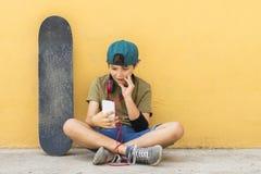 Retrato de un adolescente que se sienta en el piso en un cha del camino de la calle Fotografía de archivo libre de regalías
