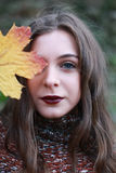 Retrato de un adolescente que sostiene una hoja de oro a su cara Imágenes de archivo libres de regalías