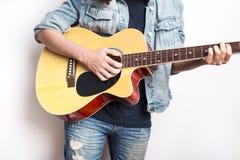 Retrato de un adolescente que toca la guitarra en chaqueta de los vaqueros del estudio que lleva Fotos de archivo libres de regalías