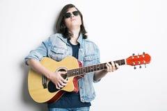 retrato de un adolescente que toca la guitarra en estudio mientras que lleva las gafas de sol y la chaqueta de los vaqueros Foto de archivo