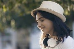 Retrato de un adolescente sonriente con un sombrero y los auriculares Imagen de archivo