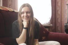 Retrato de un adolescente sonriente de la muchacha en casa que se sienta en el sofá Foto de archivo
