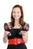 Retrato de un adolescente sonriente que sostiene los zapatos del tacón alto aislados Fotos de archivo