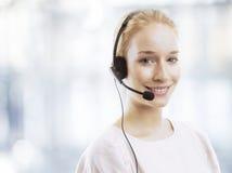 Agente femenino joven confiado del servicio de atención al cliente con las auriculares Fotografía de archivo