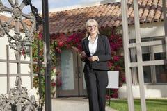 Retrato de un agente inmobiliario mayor que camina con el tablero delante de la casa Imagen de archivo libre de regalías