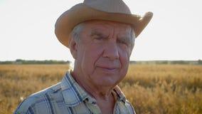 Retrato de un agrónomo caucásico mayor del granjero en un sombrero de vaquero en el campo almacen de video