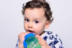 Retrato de un agua potable del niño lindo de la botella Fotografía de archivo