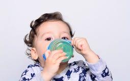 Retrato de un agua potable del niño lindo de la botella Foto de archivo libre de regalías