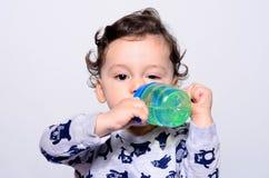 Retrato de un agua potable del niño lindo de la botella Imagenes de archivo