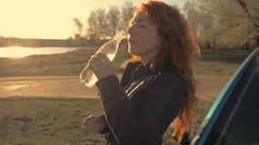 Retrato de un agua potable de la mujer joven en un fondo de la naturaleza almacen de metraje de vídeo