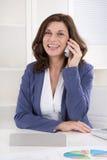 Retrato de un alto directivo de sexo femenino que llama en el escritorio imágenes de archivo libres de regalías