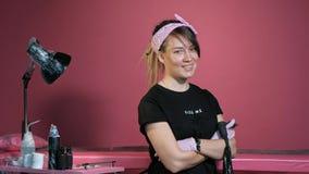 Retrato de un amo femenino atractivo del tatuaje Muchacha elegante con los dreadlocks en un fondo rosado almacen de metraje de vídeo