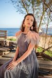 Retrato de un anhelo que sueña a la chica joven en un vestido gris con las plumas y los pendientes rosados que miran hacia fuera  Imagenes de archivo