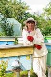 Retrato de un apicultor de la mujer con la flor Imagenes de archivo