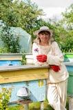 Retrato de un apicultor de la mujer con la flor Fotos de archivo libres de regalías