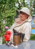 Retrato de un apicultor de la mujer con la flor Foto de archivo libre de regalías